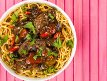 Beef and Black Bean Sauce With Red Peppers And Egg Noodles. Against A Pink Wooden Background royalty free stock images