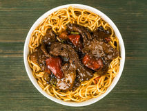 Beef and Black Bean Sauce With Red Peppers And Egg Noodles. Against A Green Wooden Background stock photography