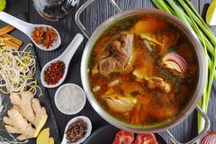 Beef bone broth in a pan. Beef bone broth and other ingredients for classic Vietnamese soup Pho Bo, with raw beef, soy sprouts, baked shallots, rice noodle, fish stock photos