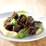 Beef Bourguignon. Rich and savoury beef bourguignon with mashed potatoes and baby salad leaves on a white plate on wooden surface Royalty Free Stock Photo