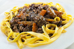 Beef bourguignon casserole. With pasta on white plate Stock Photos