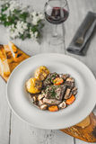Beef bourguignon in a ceramic dish on a wooden stand Royalty Free Stock Photo