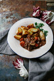 Beef bourguignon in ceramic plate. With baked potatoes on metallic background. Rustic concept, natural light Royalty Free Stock Images