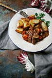 Beef bourguignon in ceramic plate. With baked potatoes on metallic background. Rustic concept, natural light Stock Photos