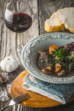 Beef bourguignon in a ceramic plate with a glass of wine Stock Image