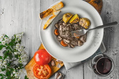 Beef bourguignon in a ceramic plate, red wine and white flowers Stock Image