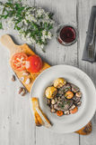Beef bourguignon in a ceramic plate, stand and white flowers Stock Images