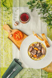 Beef bourguignon in a ceramic plate, tablecloth, fork, flowers Royalty Free Stock Photos