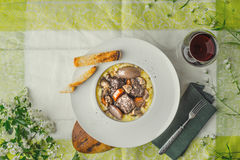 Beef bourguignon in a ceramic plate on a tablecloth and white fl Royalty Free Stock Image