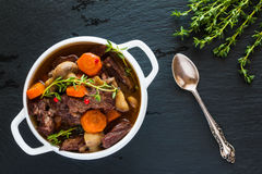 Beef Bourguignon in a white soup bowl on black stone background, top view. Stew with carrots, onions, mushrooms, bacon Royalty Free Stock Photography