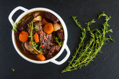 Beef Bourguignon in a white soup bowl on black stone background, top view. Royalty Free Stock Photography