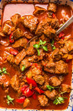 Beef braised in red tomato paprika sauce with spoon, top view Stock Image