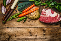 Beef brisket with vegetables ingredients for soup or broth cooking on rustic wooden background, top view Royalty Free Stock Images