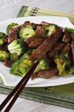 Beef with broccoli on a plate closeup and chopsticks. vertical Stock Images