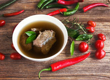 Beef broth with meat in white bowl with vegetables on wooden table Stock Photos