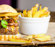 Beef burger with bacon, cheddar, homemade fries Royalty Free Stock Images
