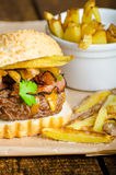 Beef burger with bacon, cheddar, homemade fries Stock Photography