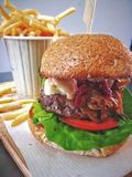 Beef burger with chips in background on wood tray stock photos