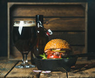 Beef burger with crispy bacon, fresh vegetables and dark beer Royalty Free Stock Photo