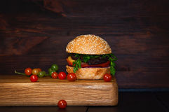 Beef Burger with cutlet and vegetables served on a chopping boar royalty free stock photos
