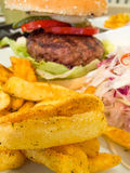 Beef burger with french fries and sliced raw cabbage. Beef burger with french fries and sliced cabbage Royalty Free Stock Photo