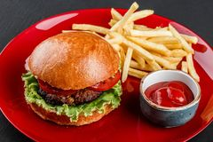 Beef burger and french fries with tomato sauce on red plate over dark background. Unhealthy food stock images
