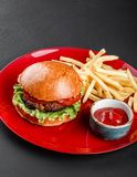 Beef burger and french fries with tomato sauce on red plate over dark background. Unhealthy food stock photos