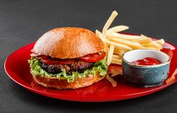 Beef burger and french fries with tomato sauce on red plate over dark background. Unhealthy food royalty free stock images