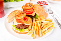 Beef burger and onion rings. Beef burger with onion rings and french fries on the plate Stock Photo