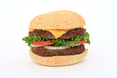 Beef burger over white. Beef burger in a bun, over white, with lettuce salad, tomato, onion, close up, macro Royalty Free Stock Image