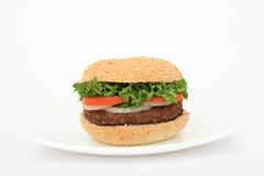Beef burger over white on a plate. Fast food beef burger on a plate over white, lettuce, onion, tomato, in a bun, with copy space Royalty Free Stock Images