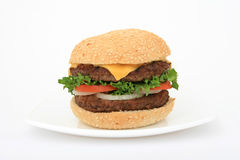 Beef burger over white on a plate. Fast food beef burger on a plate over white, lettuce, onion, tomato, in a bun, with copy space Royalty Free Stock Photo