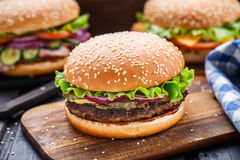 Beef burger. With pickles, red onion, mustard and fresh salad leaf Royalty Free Stock Photo