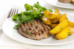 Beef burger with the roasted potato, side salad and spices on wh Stock Images