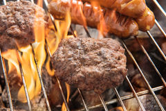Beef burger and sausages cooking over flames on grill Stock Photos