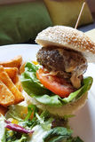 Beef burger served with potato and vegetable. A tall beef burger served with thick beef patty, sesame seed buns and along with it are some potato and vegetables Stock Photography