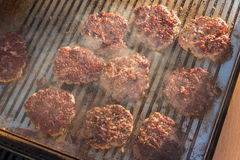 Beef burgers being grilled on barbecue. Stock Photography