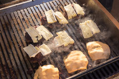 Beef burgers being grilled on barbecue. Stock Photos