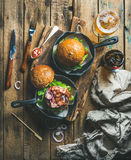 Beef burgers in cast iron pans and glass of beer Stock Photos