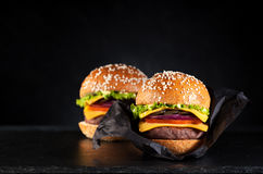 Beef burgers or cheeseburgers. In paper on black chalkboard stock image