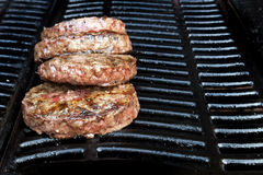Beef burgers cooking on the barbecue Stock Photo