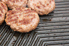 Beef burgers cooking on a griddle Stock Images