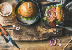 Beef burgers with crispy bacon, fresh vegetables, glass of beer Stock Photo