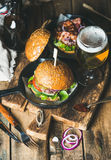 Beef burgers with crispy bacon, fresh vegetables and wheat beer Royalty Free Stock Images
