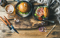 Beef burgers with crispy bacon, vegetables, glass of beer Royalty Free Stock Photo