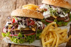 Beef burgers with fresh vegetables, microgreen, cheddar cheese and sauce served with french fries close-up. horizontal stock image