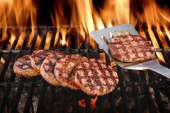 Beef Burgers On The Hot Flaming BBQ Charcoal Grill Stock Image