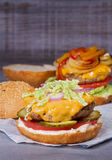 Beef burgers with red, yellow peppers, napa cabbage and cheddar. Royalty Free Stock Photography