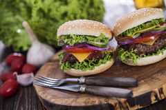 Beef burgers on a wooden board with aromatic spices Royalty Free Stock Images
