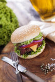 Beef burgers on a wooden board with chips and aromatic spices. Stock Image